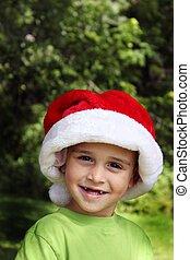 Cute little boy missing two front teeth wearing santa hat