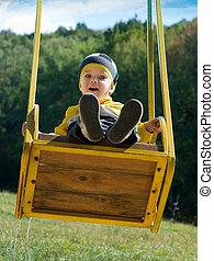 Cute little boy on a swing