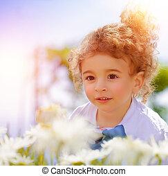 Cute little boy on daisy field