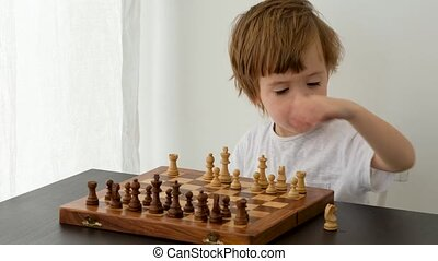 Cute little boy playing chess - Cute boy plays chess on a ...