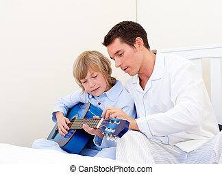 Cute little boy playing guitar with his father