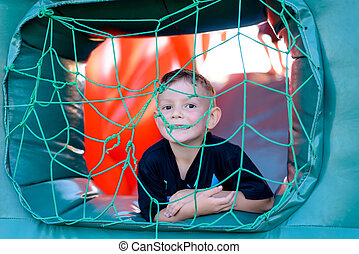 Cute little boy playing in a jumping castle
