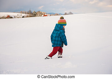 Cute little boy playing in snow field. Kid having fun outdoors, running on snow, wearing warm blue jacket, hat and scarf