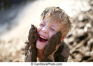 Cute Little Boy Playing Outside in the Mud with a Dirty Face