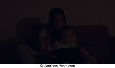 Cute little boy playing tablet with mom at night in bed in the dark.