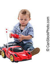 Cute little boy playing with a remote controlled car.