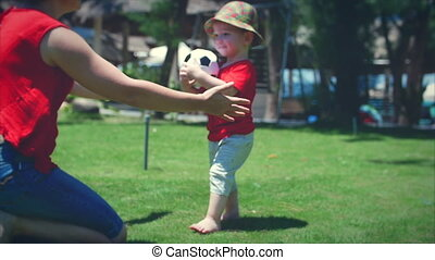 Cute little boy playing with a soccer ball running to his mother in a hug. Stock footage.