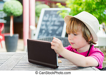 Cute little boy playing with tablet pc in a cafe