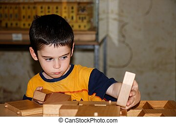 Cute little boy plays with wooden bricks and builds a house