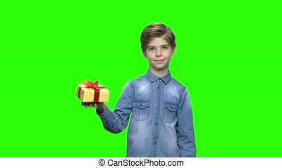 Cute little boy pointing at yellow gift box with red ribbon.