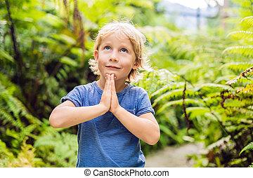 Cute little boy praying in the woods