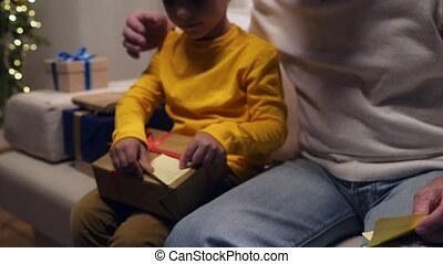 Cute little boy preparing Christmas presents with his grandfather