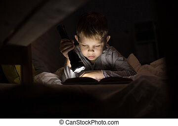 Cute Little Boy Reading with Flashlight