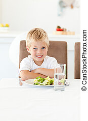 Cute little boy ready to eat his salad for lunch sitting at a table in the kitchen
