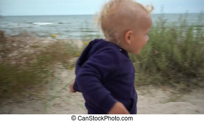 Cute little boy running toward mother and sister through ...