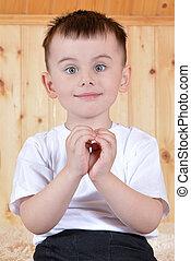 Cute little boy showing a heart
