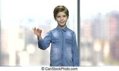 Cute little boy showing ok sign. Handsome caucasian child in denim jacket giving ok symbol while standing on blurred background.