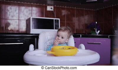 Cute Little boy sits in a chair and eats fruit for breakfast