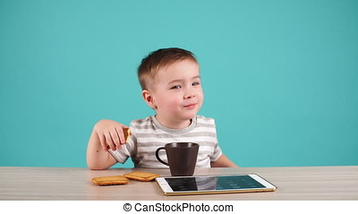 Cute little boy sitting at table and playing on tablet. Child is drinking tea.
