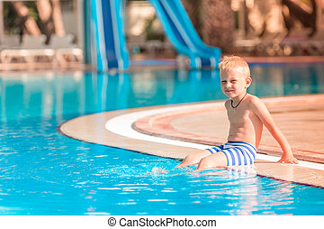 Cute little boy sitting at the pool