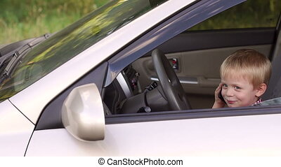 Cute little boy sitting behind the wheel of cars and playing with the phone.