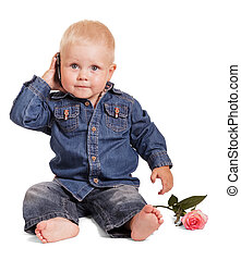 Cute little boy sitting holds mobile phone, rose isolated.