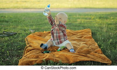Cute little boy sitting on a blanket in the park. Baby less than a year and he played