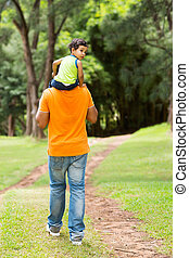 cute little boy sitting on father's shoulders outdoors