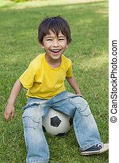 Cute little boy sitting on football at park