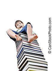 Cute little boy sitting on heap of textbooks