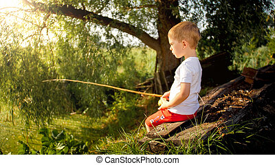 Cute little boy sitting on the bench at river and fishing ...