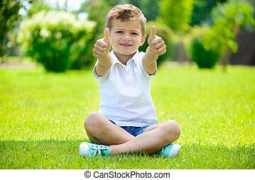 Cute little boy sitting on the grass