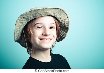 cute little boy smiling on green teal background