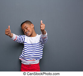Cute little boy smiling with thumbs up sign
