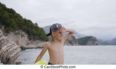 Cute little boy stand on the rock and look out over the sea at the sunset. Portrait of a cute boy with inflatable ring who looking at sea waves. Summer vacation in the 7-8 years boy