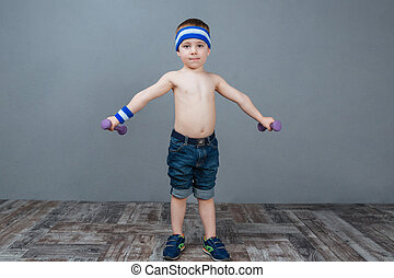 Cute little boy standing and working out using dumbbells...