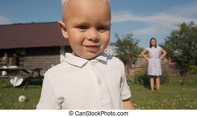 Cute Little Boy Standing In Front of Camera In The Garden In Summer. Mom On Background