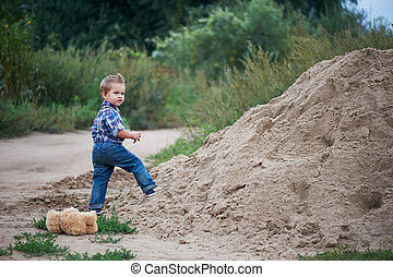 Cute little boy standing near a big pile . Memories of childhood and carefree