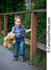 Cute little boy standing near a brown wooden , stylish jeans with suspenders and plaid shirt . Memories of childhood carefree