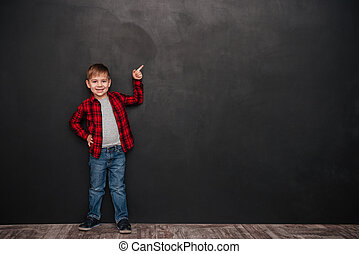 Cute little boy standing over chalkboard and pointing up