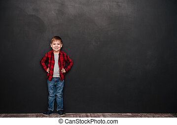 Cute little boy standing over chalkboard