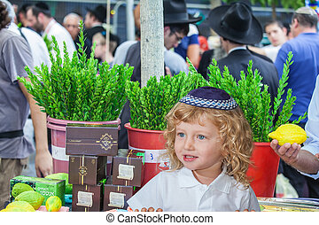 Cute little boy stands on pre-holiday market