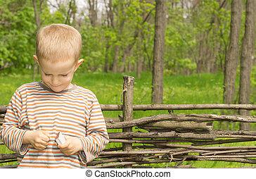 Cute little boy struggling to light a match