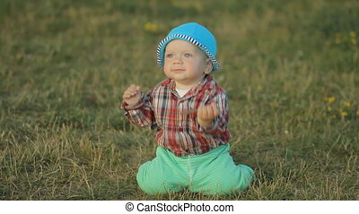 Cute little boy takes the first steps in the park on the grass