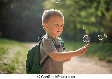 Cute little boy touching a soap bubble playing in the park