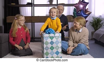Cute little boy unwrapping gift box with present