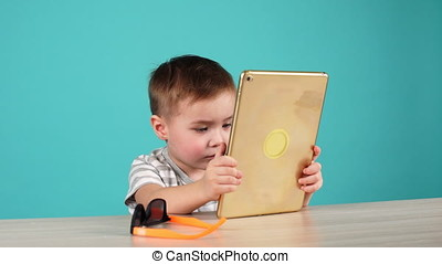 Cute little boy uses tablet sitting at table, isolated on blue.