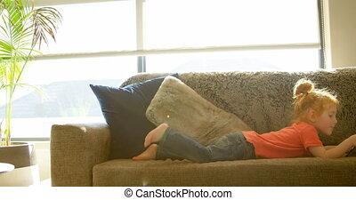 Cute little boy using digital tablet in living room at home 4k