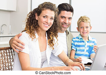 Cute little boy using laptop with parents at table at home...
