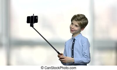 Cute little boy using selfie stick. Handsome child with...